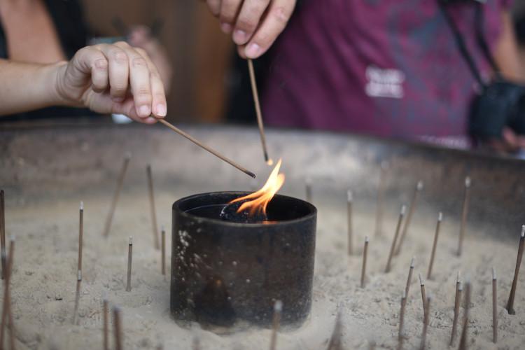 person lighting incense stick